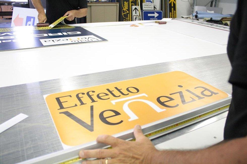 un cartello con scritto Effetto Venezia su un piano da lavoro in uno stampificio