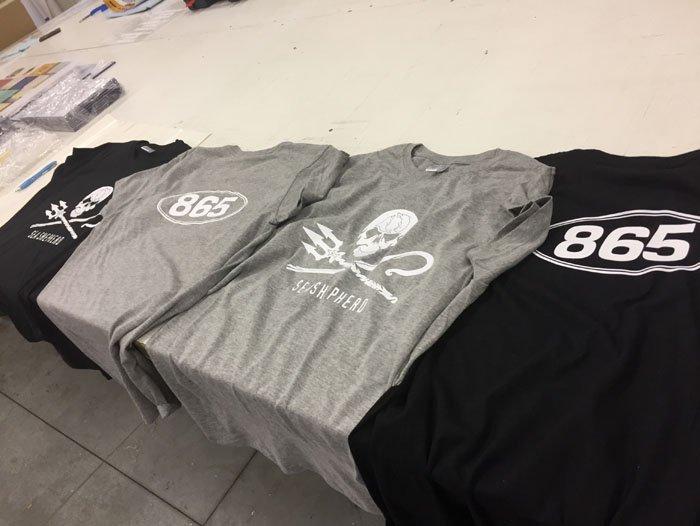 Magliette di colore nero e grigio sul tavolo
