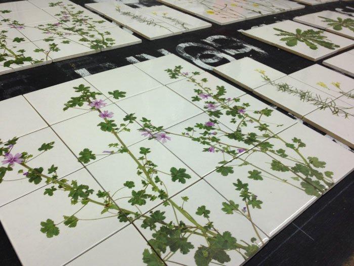 Piastrelle bianche con fiori viola e foglie verdi