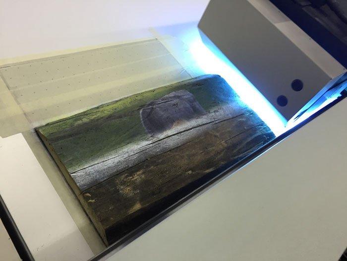 vista laterale di stampante con foglio di legno