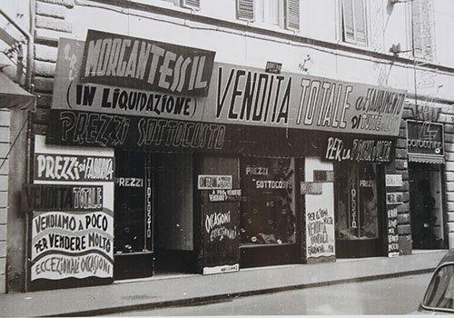 immagine in bianco e nero con vista di un negozio e delle insegne pubblicitarie