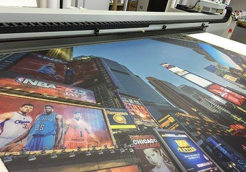 un poster accanto a una stampante con immagini di palazzi e cartelli pubblicitari