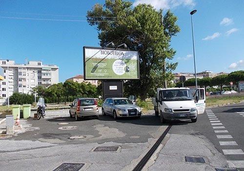 un cartello pubblicitario con scritto Biobottega e accanto delle macchine parcheggiate