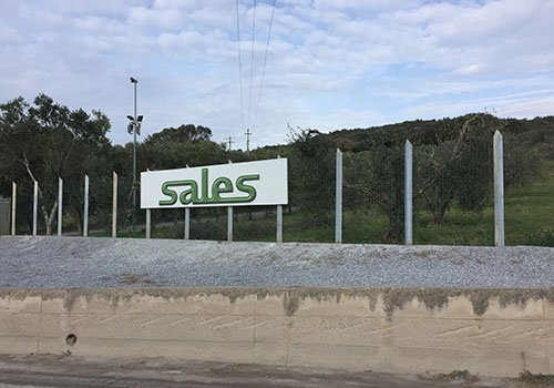 una recinzione e un cartello con scritto Sales