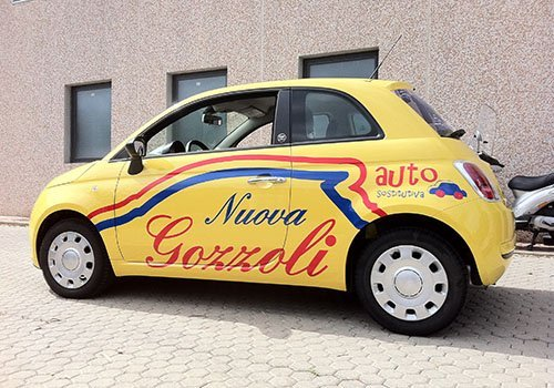 una Fiat 500 di color giallo con scritto Nuova Gozzoli