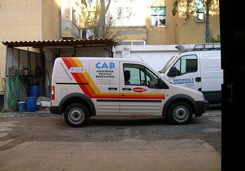 un furgone bianco con scritto Cab Assistenza Tecnica Bruciatore