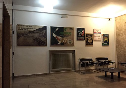una sala con due sedie e dei quadri al muro