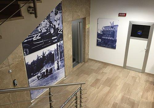 un corridoio e dei poster con delle macchine da corsa antiche sul muro
