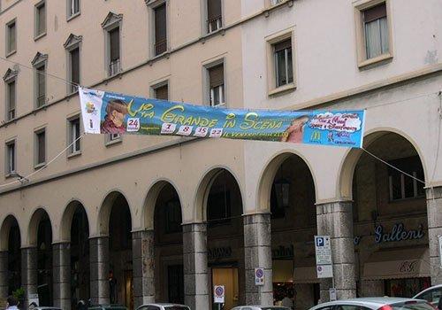 un vicolo cittadino e uno striscione  appeso con scritto Via Grande in Scena