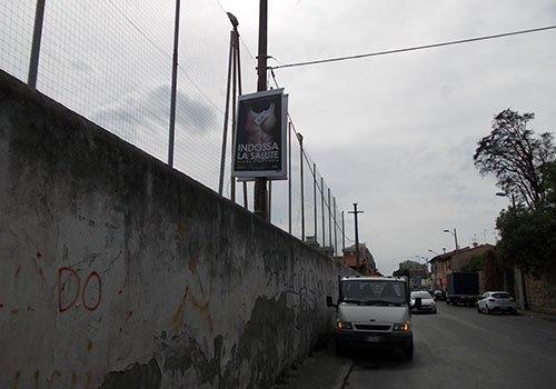 un muro alto con sopra un manifesta con scritto Indossa La Salute