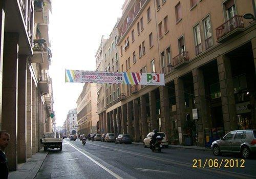 una strada con i palazzi sui lati e uno striscione del PD appeso