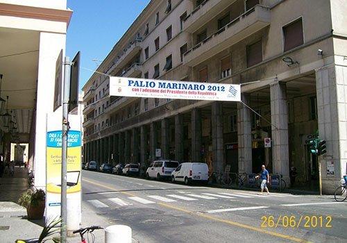 un uomo che attraversa la strada e uno striscione appeso con scritto Palio Marinaro 2012
