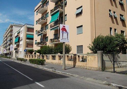 due palazzi residenziali e un palo con un manifesto con l'immagine di una ballerina