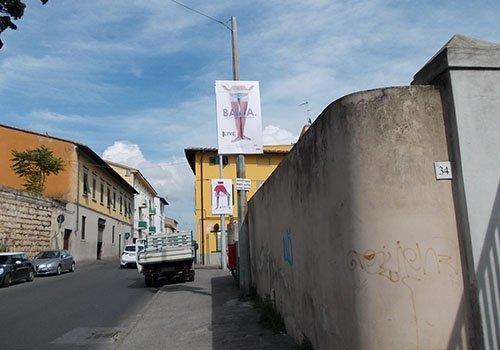 una strada con vista delle ville e un palo con un manifesto con  scritto Balla