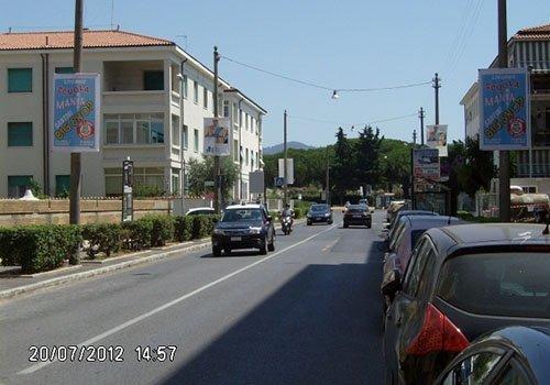 una strada con delle macchine parcheggiate e dei pali con dei manifesti