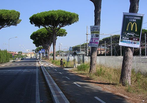 una strada con gli alberi sui lati e dei manifesti con scritto Via Montanara Cecina Mcdrive