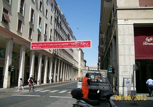 una strada cittadina con un manifesto di color rosso