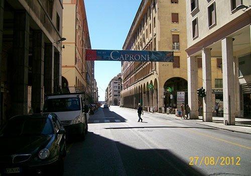 una strada cittadina con un manifesto con scritto Caproni