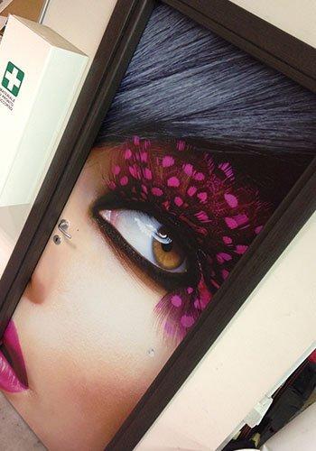 un quadro con l'immagine di un occhio di una donna  con delle ciglia fucsia
