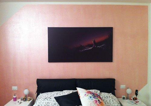 un quadro appeso al muro e un letto