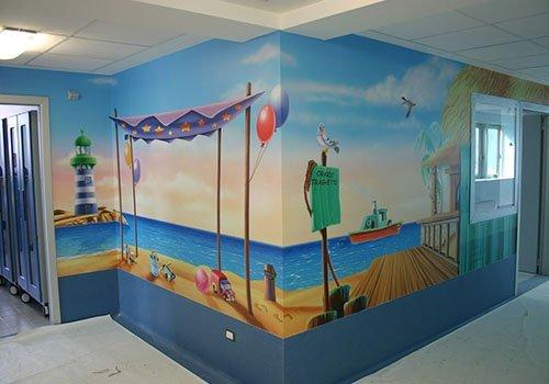 dei muri con un dipinto di mare,  spiaggia e giocattoli
