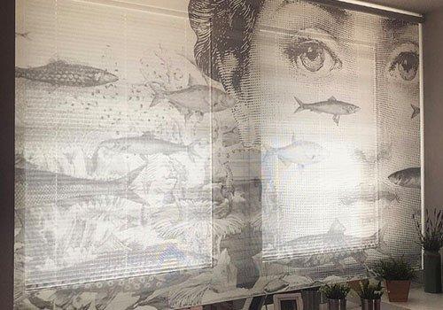 una tenda con dei disegni di alcuni  pesci e il viso di una donna