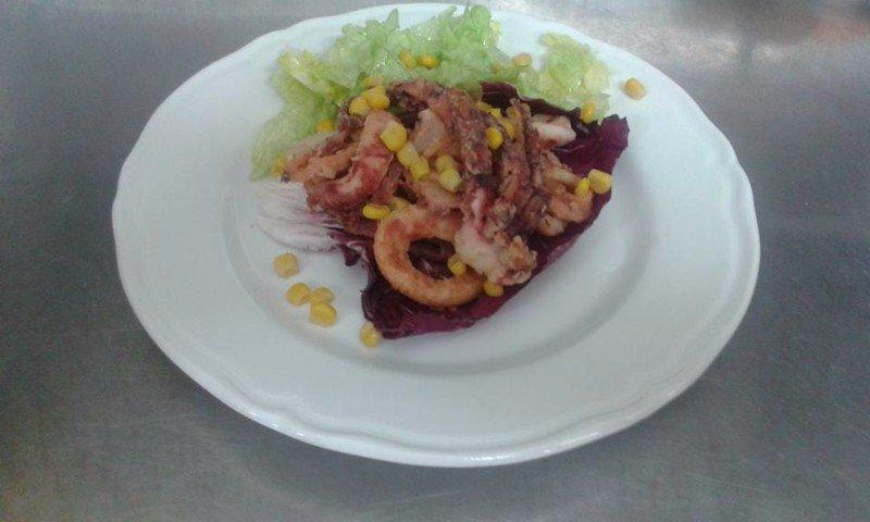 un piatto di polipo, calamari fritti, insalata e mais