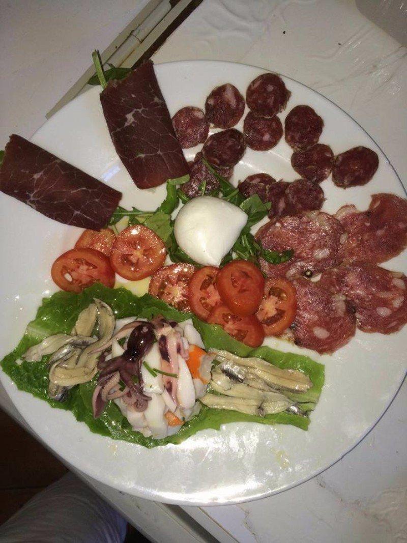 un piatto con affettati, formaggi e alcune pesci