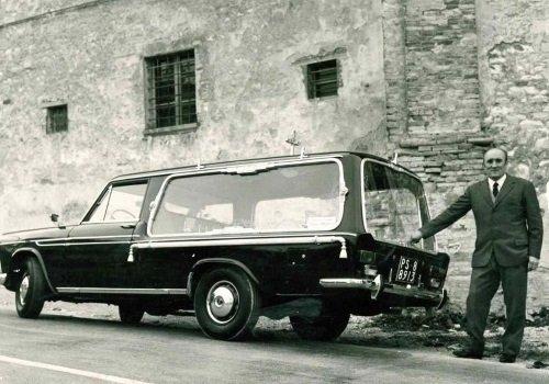 una foto in bianco e nero di un signore vicino a un vecchio carro funebre