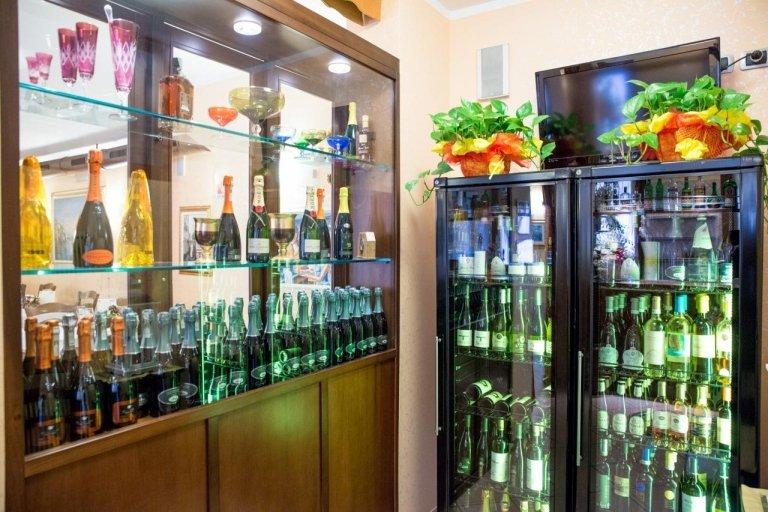 Frigo e vetrina piene di diverse varietà di vini
