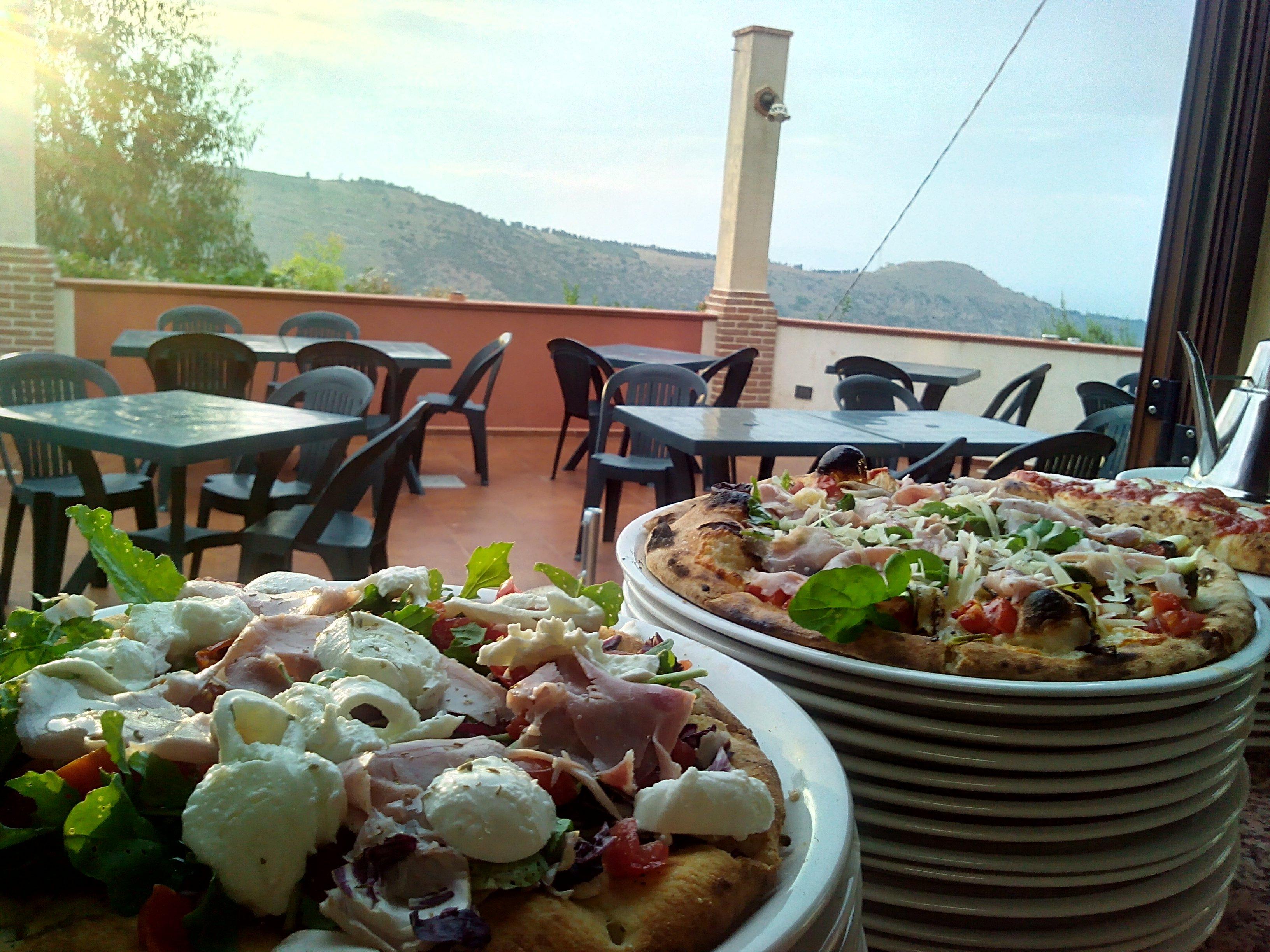 Due pizze ricche di ingredienti su due piatti di fronte alla terrazza del ristorante