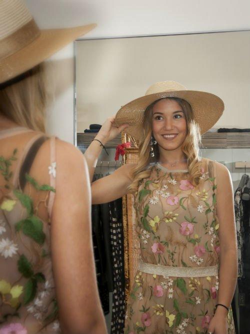 una ragazza con un cappello si guarda allo specchio