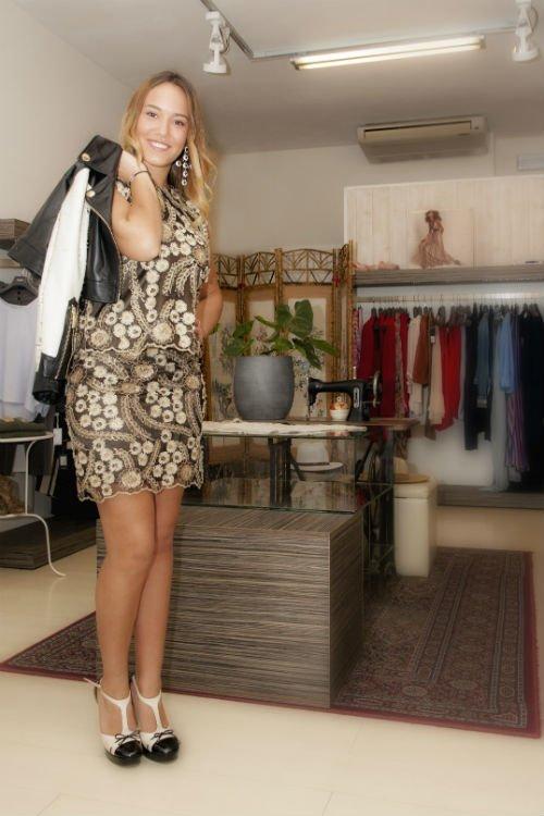 una ragazza con un abito con i disegni di fiori in un boutique
