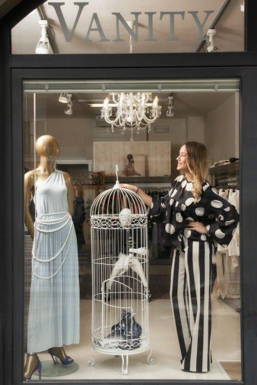 una vetrina con un manichino con un abito azzurro e una modella accanto