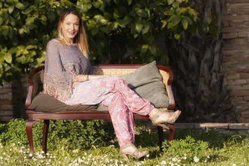 una donna con dei pantaloni rosa e una mantella di color viola seduta su una panca