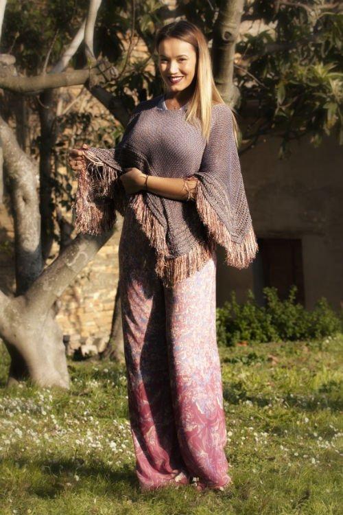una donna con dei pantaloni rosa e una mantella di color viola