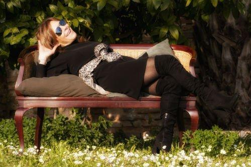 una donna con un abito nero in posa su una panca