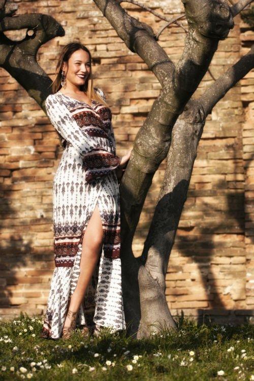 una donna con un abito lungo in posa accanto un albero
