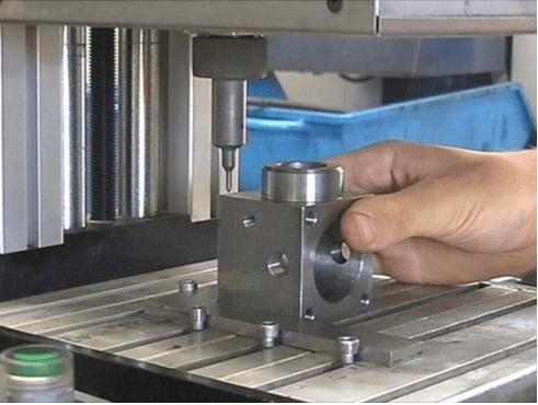 Foratura di un cubo di metallo