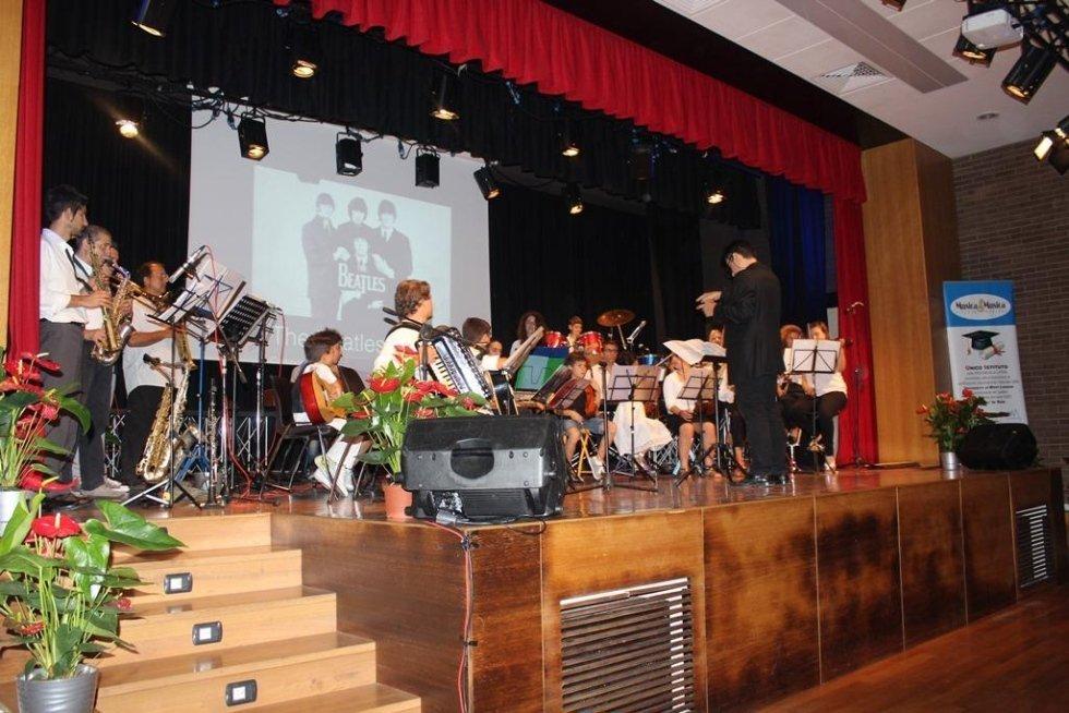 Orchestra su palcoscenico con direttore d'orchestra