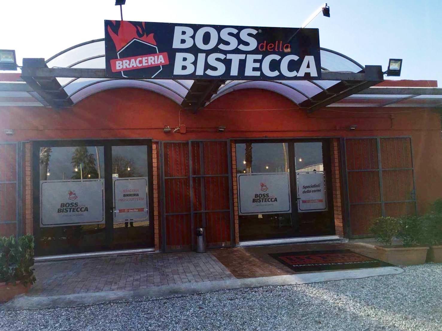 esterno di un edificio di color rosso con sopra un' insegna con scritto Braceria Boss della Bistecca e vicino all'entrata dei vasi con delle piante un posacenere in metallo e un tappeto