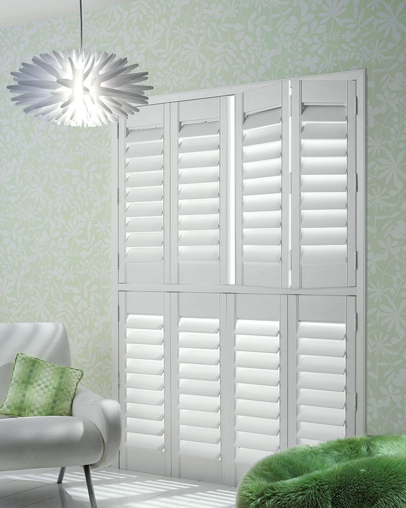 white wooden shutters in green bedroom