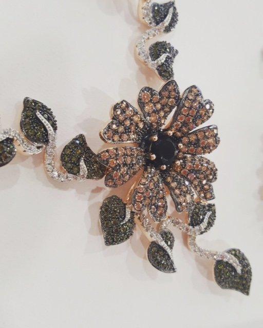 collana in argento con foglie nere e fiore colorato al centro