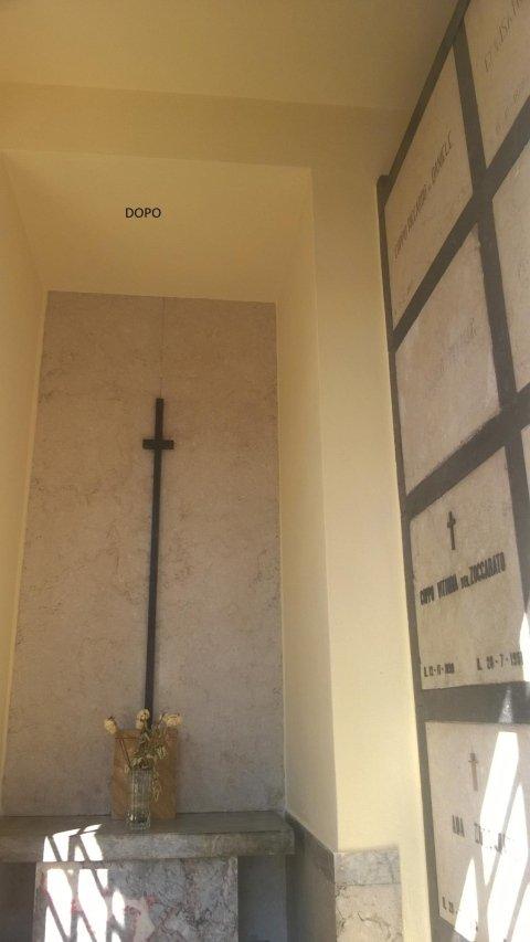 un muro verniciato di giallo con una croce e sotto un altarino in pietra con un vaso di fiori