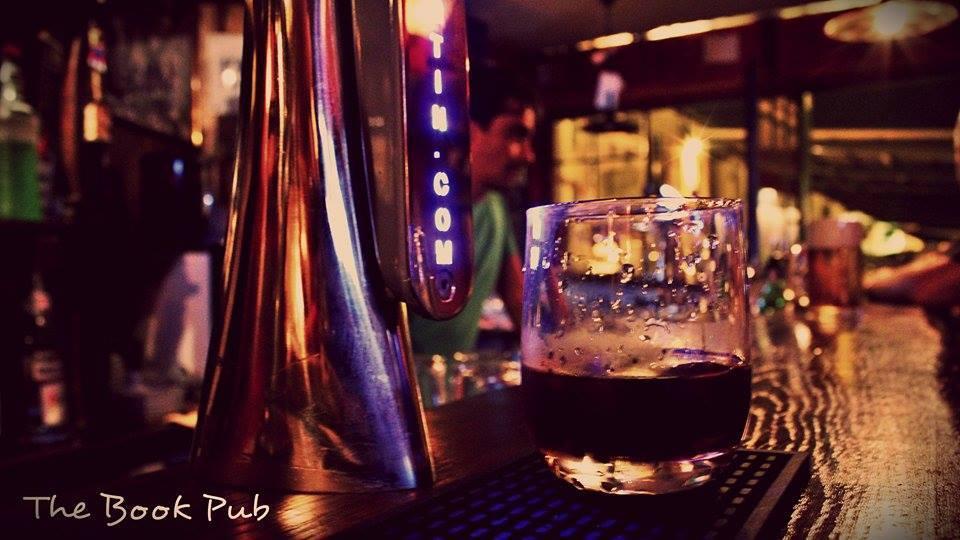 bicchiere di birra accanto a spillatore
