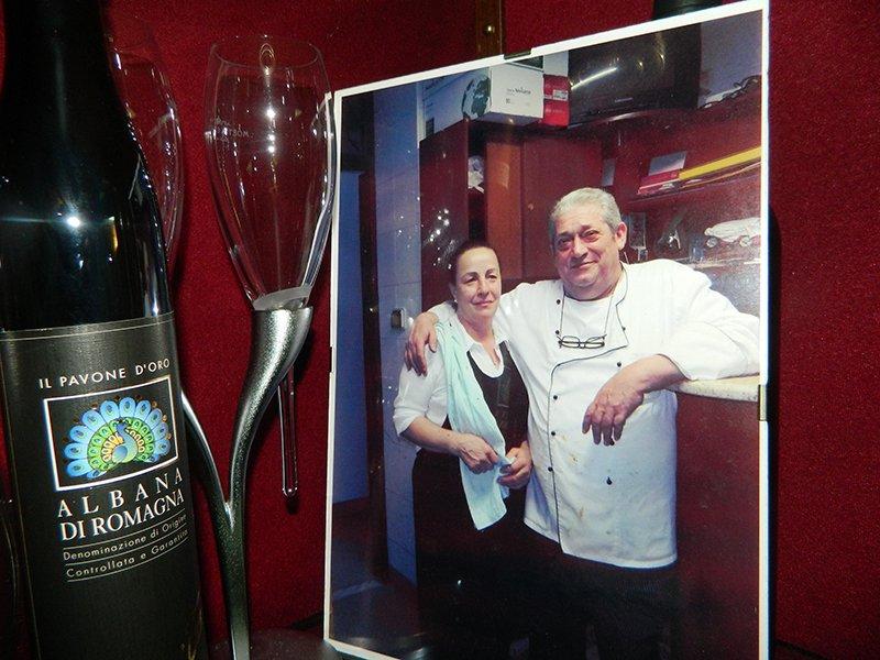 una foto di un cuoco che abbraccia una donna e accanto una bottiglia di vino e due bicchieri