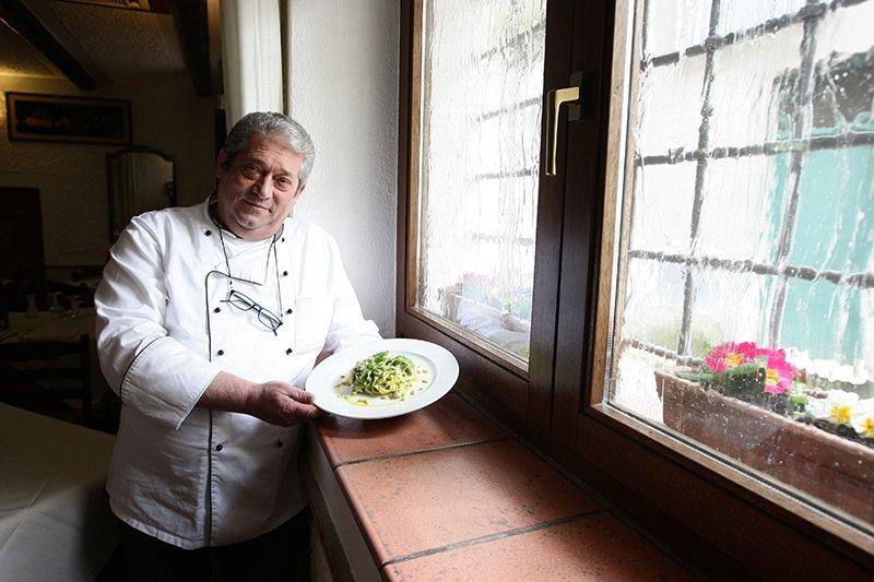 un cuoco che mostra un piatto di tagliatelle al pesto