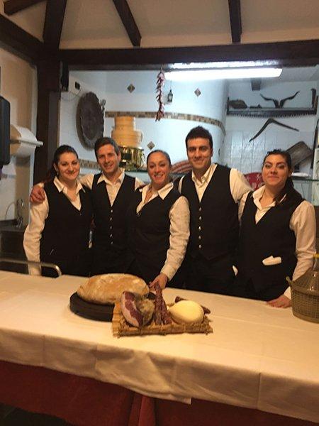 dei camerieri in posa per una foto e davanti un tavolo con del pane e un tagliere di salumi e formaggi