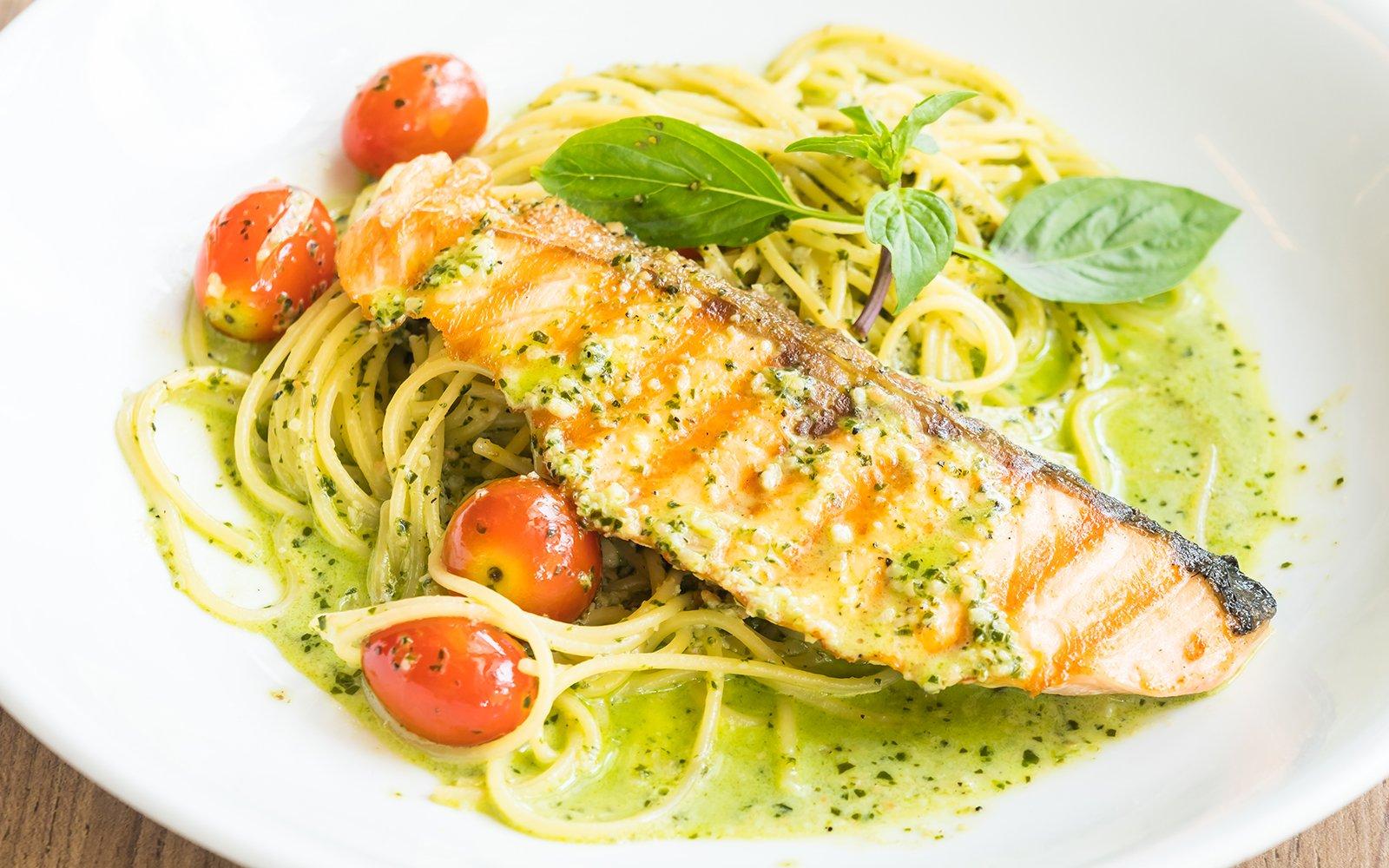 un piatto di spaghetti con il pesto,pomodorini e sopra un trancio di salmone ai ferri