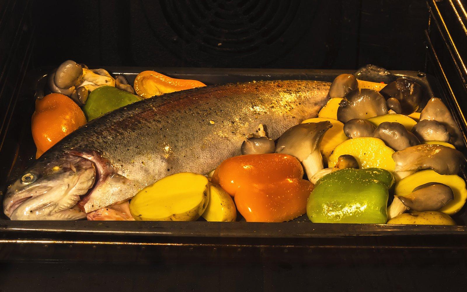 Cottura di una trota e verdure in forno